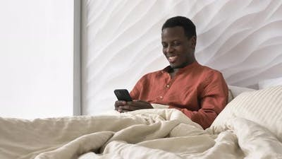 AfricanAmerican Man Laughs Reading Phone Message in Bed