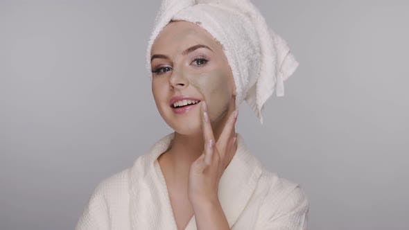 Thumbnail for Girl in Bathrobe Applying Facial Clay Mask and Smoothes on Her Face