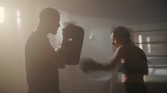 Young Woman Athlete in Boxing Gloves and Sport Clothes is Boxing With Her Skillful Trainer
