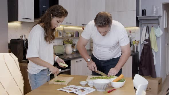 Attractive Couple Cooks Together Slicing Onions and Zucchini According To Recipe