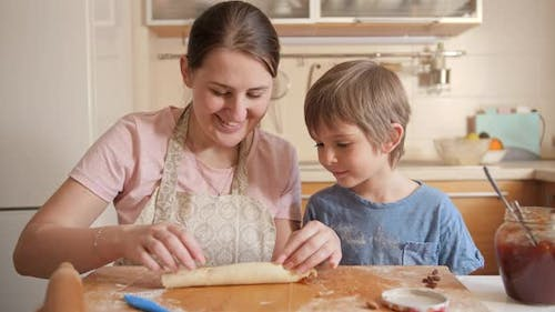 Young Mother Teaching Her Little Son Baking Sweet Roll with Jam Filling