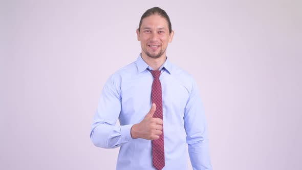 Cover Image for Happy Handsome Businessman Giving Thumbs Up