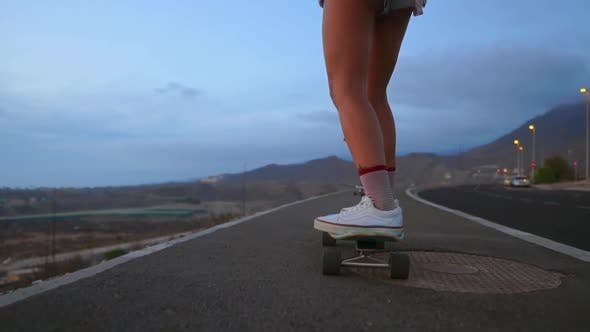 Cover Image for Woman Skateboarder Rides on a Board on the Slope Against the Sky From the Mountain