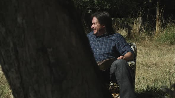 Dolly shot of a man and woman talking and sitting on a couch in the middle of a forest clearing