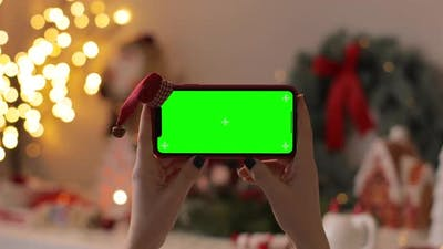 Girl Hands holding the iPhone Xr smartphone in horizontal orientation with green screen