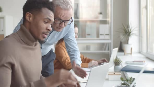 Thumbnail for Senior Male Mentor Giving Feedback to Young Black Trainee in Office