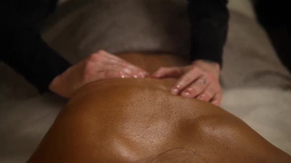 Thumbnail for Close Up Spa Hotel Massage Woman Back. Therapist Hands Do Massage To a Woman in a Dark Room with