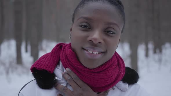Thumbnail for African American Girl Dressed Warm Wearing a Red Scarf and White Jacket Posing in the Winter Forest.