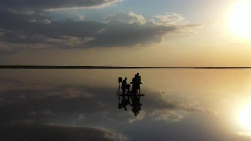 People Are Playing Music on Calm Sea with Amazing Reflections of the Sky,