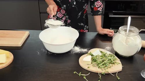 Sifting flour by sieve in bowl.
