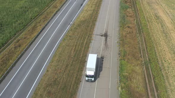 Thumbnail for Aerial Shot of Truck with Cargo Trailer Driving on Empty Road and Transporting Goods. Flying Over