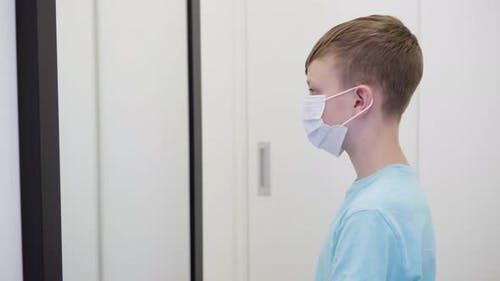 A Young Boy Puts on a Face Mask, Looks in Mirror Then Takes It Off in an Apartment