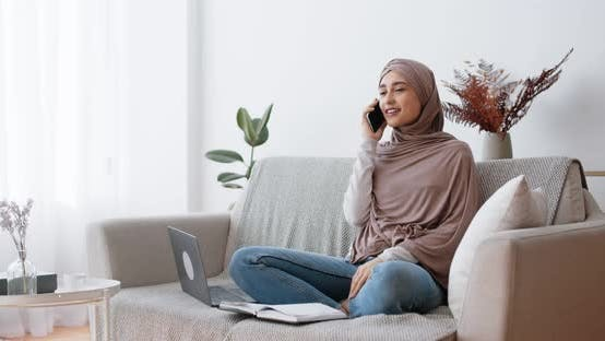 Young Muslim Woman in Hijab Working on Laptop on Computer at Home and Talking By Phone