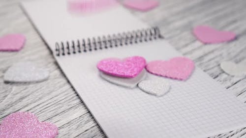 Glittering paper hearts fall on an open notebook with black metal binding