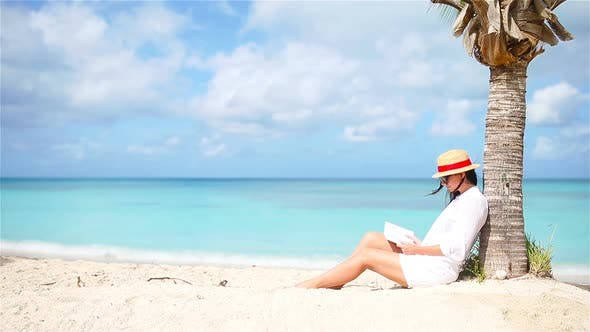 Young Woman Reading Book on White Beach Sitting Under the Palmtree