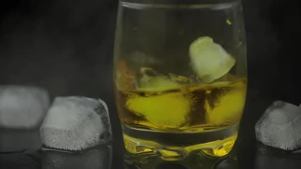 Thumbnail for Whiskey with Ice. Adding Ice Cubes on Black Background. Glass of Rum Alcohol