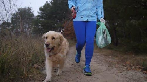 Female Runner Picking Up Litter in Autumn Forest