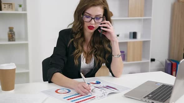 Thumbnail for Office Manager in Glasses with Stylish Look Working with Financial Reports with Graphs