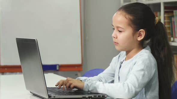 Thumbnail for Happy Beautiful Asian Little Girl Smiling While Using Laptop