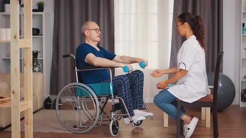 Elderly Man in Wheelchair Exercising