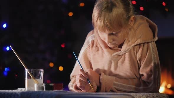 Thumbnail for Blondhaarige Mädchen malt in der Nähe des Neujahrsbaumes am Heiligabend