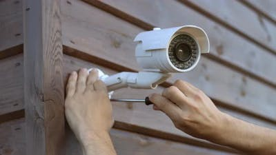 Technician installing wireless CCTV camera security system at house.