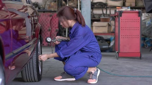 Woman inflating car tire in garage
