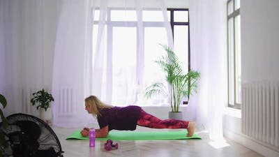Fitness Training  Blonde Overweight Woman Doing Fitness Exercises  Holding the Plank Exercise