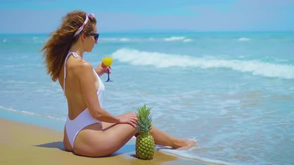 Thumbnail for Cheerful Beautiful Young Girl Are Sitting on the Beach By the Sea with Pineapple and Juice