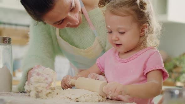Handheld-Ansicht von kleinen Mädchen rollenden Teig für Kekse. Aufnahme mit RED Heliumkamera in 8K
