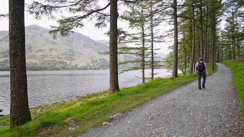 A man walking on a road by the beautiful and peaceful lake in the England Lake District - wide shot