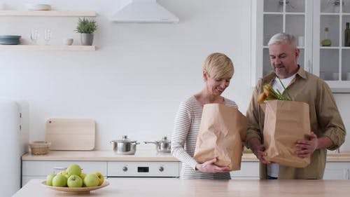 Spouses Entering Kitchen Carrying And Unpacking Groceries Shopping Bags Indoor