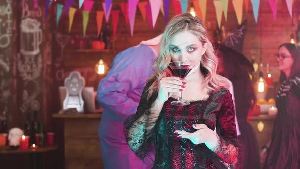Thumbnail for Young Woman Dressed in a Vampire Costume Drinks Blood at a Halloween Party