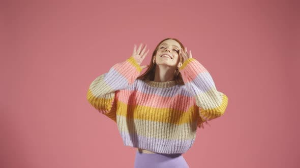 Young Female Model in a Pullover Poses for the Camera on an Isolated Background