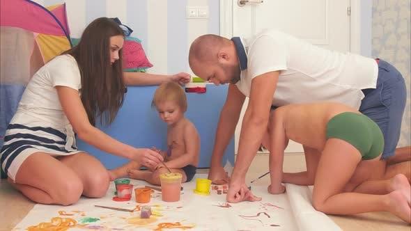 Thumbnail for Glückliche Mutter, Vater und ihre kleinen Söhne Malerei mit Aquarellen im Kinderzimmer