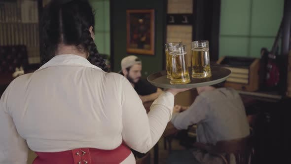 Cover Image for Cute Fat Girl with Three Glasses of Beer on a Tray in a Beer Restaurant
