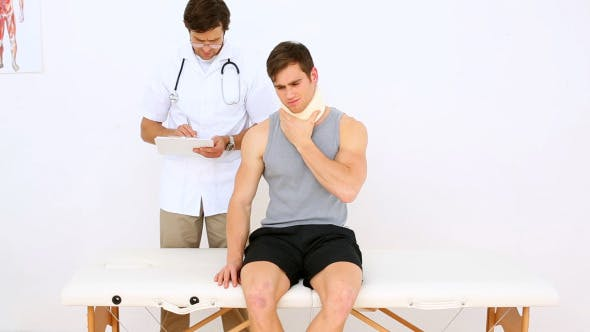 Physiotherapist Talking To Patient Wearing