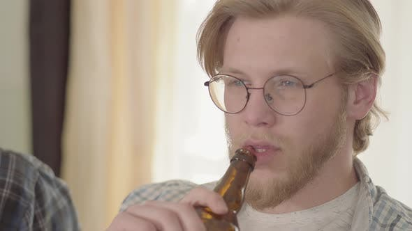 Cover Image for Portrait of the Confident Blond Man with Blue Eyes Drinking Beer Indoors Looking Away. Bearded Man