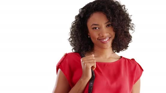 Thumbnail for Cute African female holding purse, smiling at camera in studio with copyspace
