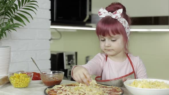 Thumbnail for Cooking Pizza. Little Child in Apron Adding Grated Cheese To Dough in Kitchen