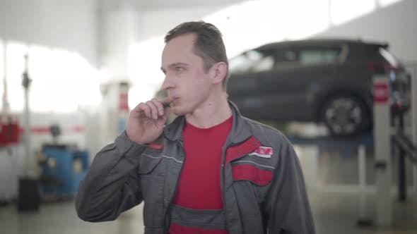 Thumbnail for Young Male Auto Mechanic Looking Around in Repair Shop and Thinking. Portrait of Caucasian