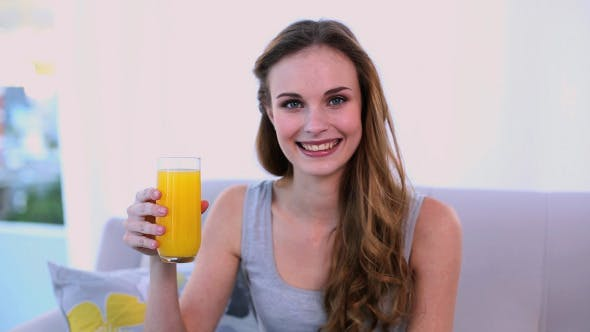 Thumbnail for Happy Model Drinking Orange Juice On The Couch