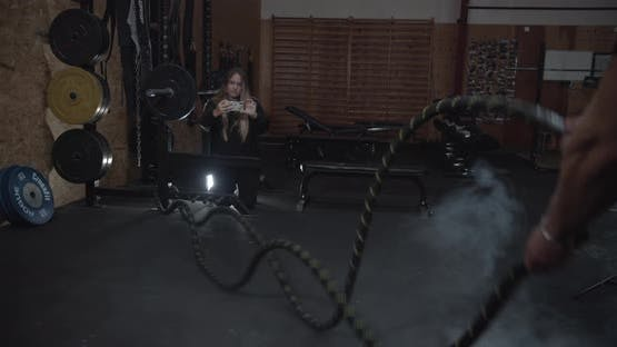 Reveal Shot of a Strong Man Doing the Battle Rope While a Girl Takes His Photos
