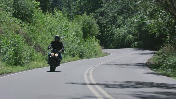 Thumbnail for Tracking shot of man riding motorcycle on country road.  Fully released for commercial use.