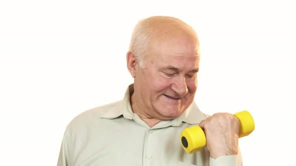 Happy Old Man Showing Thumbs Up Working Out with a Dumbbell