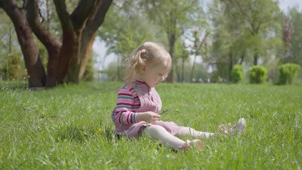 Thumbnail for Cute Little Girl Sitting on the Grass in the Park, Playing Alone, Pointing with a Tiny Finger Up