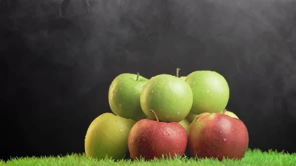 Thumbnail for Fresh apples with droplets of water against black background on rotating grass surface.