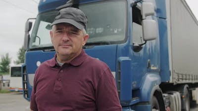 Professional Truck Driver Stands In Front Of Truck