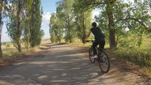 A Young Girl Rides a Bicycle Along a Forest Road.