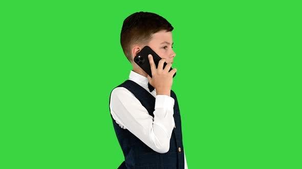 Serious Boy in einem weißen Hemd Fliege und Weste sprechen auf einem Green Screen Chroma Key